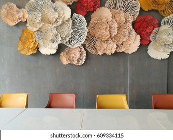 Papercut decorative object on Gray wall with white table and multicolor chairs in the foreground.