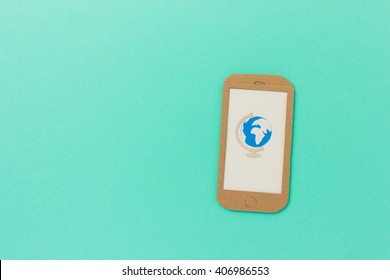 Paper-cut globe on smartphone - mobile travel app image with space for text