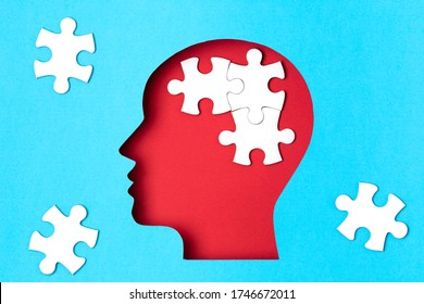 Papercut head with jigsaw puzzle pieces inside. Mental health problems, psychology, memory, logic, thinking process, solution, mental illness concept