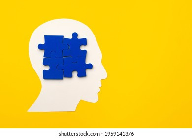 Papercut head silhouette with puzzle pieces on yellow background