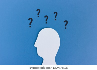 Papercut silhouette of human head with many question marks above head on blue background