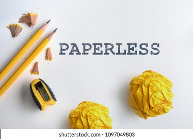 PAPERLESS text and Yellow pencil and yellow crumpled paper with shaving on white drawing watercolor paper