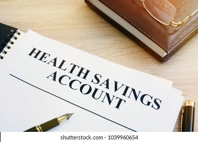 Papers about Health savings account (HSA) on a desk.