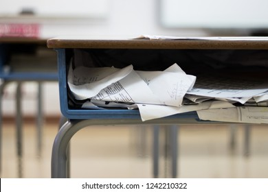 Papers and binders within a school classroom desk