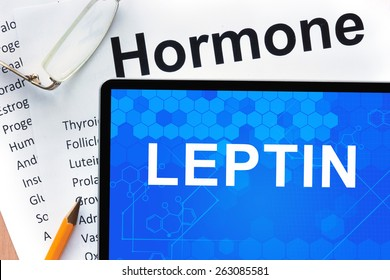 Papers with hormones list and tablet  with word leptin.