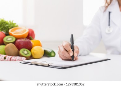 Paperwork. Doctor nutritionist writing on paperwork in office, filling patient health history, copy space