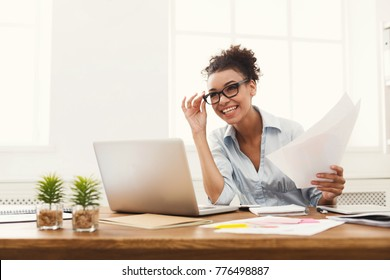 Paperwork. Happy smiling african-american business woman in formal wear sitting at wooden desk in modern office and reading report document.