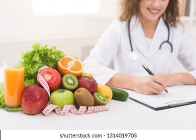 Paperwork. Nutritionist writing diet plan, sitting at workplace with vegetables, free space