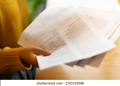 Paperwork in woman hand for singing after posing action. Model evidence document to support her occupation after work with photographer group in Studio. Endorsed release papers for professional model
