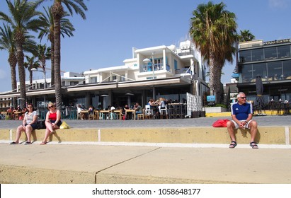 Paphos, Cyprus - 15 March 2018: Tourists sat on the wall of the promenade in the town of Paphos Cyprus with people eating in seafront restaurants