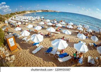 PAPHOS, CYPRUS - August 20, 2017: Rows of beach lounges and sun umbrellas on a Coral Bay beach near Peyia village.