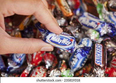 Paphos, Cyprus - December 19, 2013 Milky Way candy in woman's hand with background of Snickers, Mars, Twix, Bounty, Galaxy, and Maltesers Teasers candies. All candies manufactured by Mars, Inc.