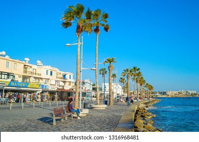 PAPHOS, CYPRUS - FEBRUARY 13, 2019: People on Paphos promenade at sunset. Paphos is the famous tourist destination in Cyprus