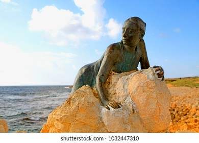 PAPHOS, CYPRUS - JANUARY 12, 2018: A bronze statue of woman called 'Sol Alter' by Yiota Ioannidou on a stone located on sea promenade, Paphos, Cyprus. Selective focus