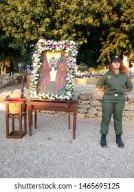 Paphos, Cyprus - June 29, 2019: Icon of St. Paul and Barnabas decorated by a garland and guarded by a service woman before the liturgy on the Apostle Paul feast day