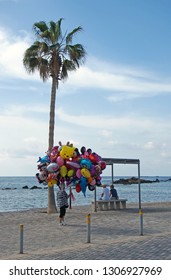 Paphos, Cyprus - March 17, 2018: a balloon seller walks past two tourists sat on the beach in Paphos cyprus