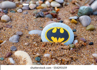 Paphos, Cyprus - November 22, 2016 Pebble with painted sign Batman lying on the beach with sand and stones.
