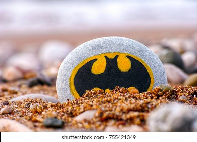 Paphos, Cyprus - November 22, 2016 Pebble with painted sign Batman on the beach with sand and stones. Closeup.