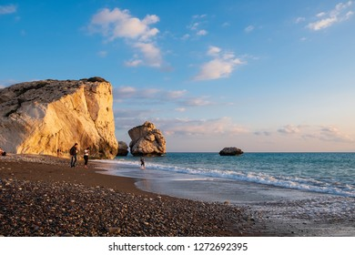 Paphos, Cyprus - November 24, 2018: People enjoy themselves at the beach at Petra tou Romiou rocks bathed in afternoon light, in Paphos, Cyprus. The beach is considered to be Aphrodite's birthplace.