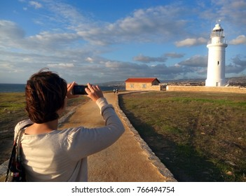 Paphos, Cyprus October 30, 2017, a tourist woman taking photos of the famous Paphos lighthouse October 30, 2017 in Cyprus