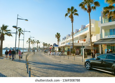 PAPHOS, CYRPUS - FEBRUARY 13, 2019: People walking by Cyprus promenade at sunset. Paphos - famous tourist destination in Cyprus