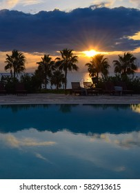 PAPHOS/CYPRUS - FEBRUARY 14 2017: Palm trees, swimming pool and beautiful sunset view from Coral Beach Hotel. Resort on the sea