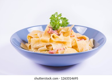 Pappardelle Carbonara with some parsley on a blue plate on a white background