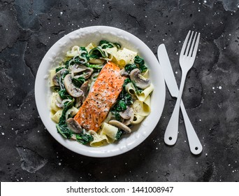 Pappardelle pasta with creamy spinach mushrooms sauce and baked salmon on a dark background, top view. Salmon florentine homemade pasta