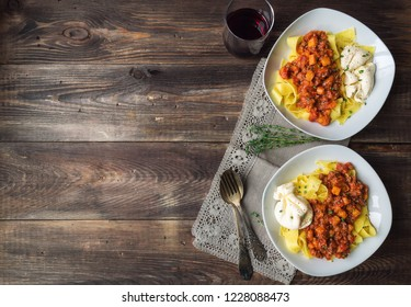 Pappardelle pasta with meat ragout with pumpkin and burrata cheese on rustic wooden background. Italian cuisine. Top view. Copy space area.