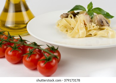Pappardelle Pasta on a white dish with mushrooms and other herbs, red chili pepper, cherry tomato isolated white