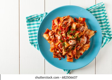 Pappardelle pasta with tuna, in tomato sauce. Served on a blue plate, white boards in the background. Top view.