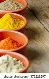 Paprika, mustard, coriander and turmeric spices on wooden background with copy-space