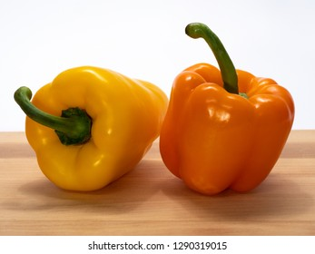 Paprika pods, yellow and orange on a cutting board