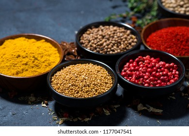 paprika, turmeric, red pepper and other fragrant spices on dark background, closeup, horizontal