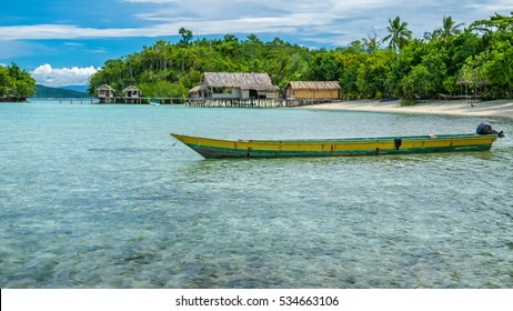 Papua Local Boat, Beautiful Blue Lagoone near Kordiris Homestay, Small Green Island and Homespay in Background, Gam, West Papuan, Raja Ampat, Indonesia