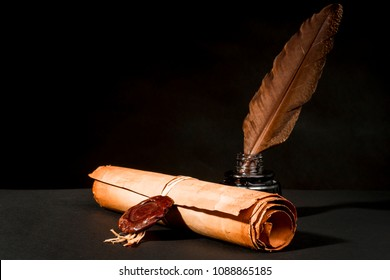 A papyrus scroll with a seal, a feather and an inkwell on a black background