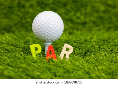 Par word with golf ball behind on green grass, In golf, par is the predetermined number of strokes that a proficient (scratch, or zero, handicap, golfer should require to complete a hole, a round ) - Shutterstock ID 1887898735