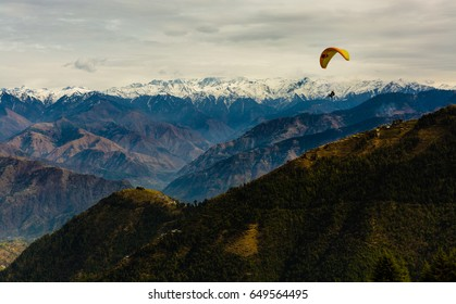 Para Gliding adventure at beautiful valley of Khajjiar near Dalhousie and Kalapathar, Himachal Pradesh, India. Himalayan Mountains in the background.