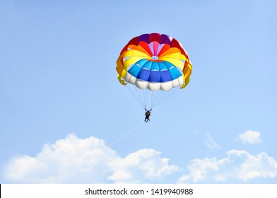 Para sailing using a parachute on background of blue cloudy sky.