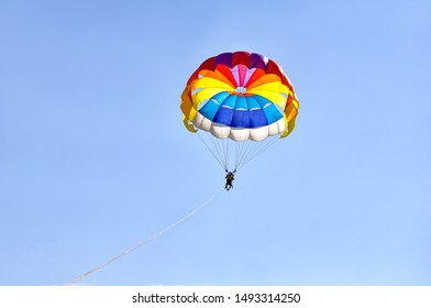 Para sailing using a parachute on background of blue sky.