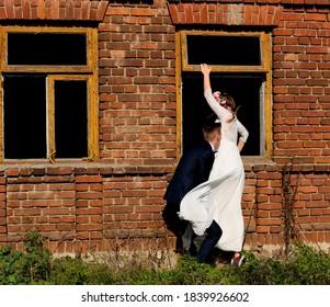 para ślubna wchodzi przez okno do domu - Shutterstock ID 1839926602