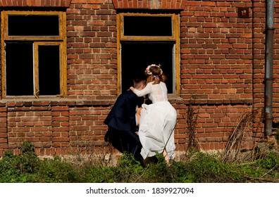 para ślubna wchodzi przez okno do domu - Shutterstock ID 1839927094
