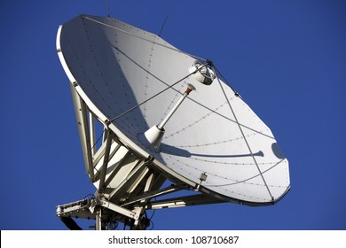 A parabolic satellite dish with blue sky and sunny day