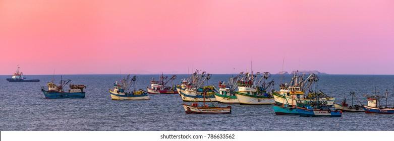 PARACAS, ICA, PERU - CIRCA 2012: A group  boats at the sunset circa 2012, in Paracas, Peru.