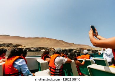 Paracas, Peru - February 15, 2018: Tourist woman takes a photograph with her cell phone from the Candelabra geoglyph from a boat while traveling to the Ballestas Islands