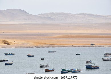 Paracas, Peru February 2020 Fishing boats in bay near the town and hills in the background.