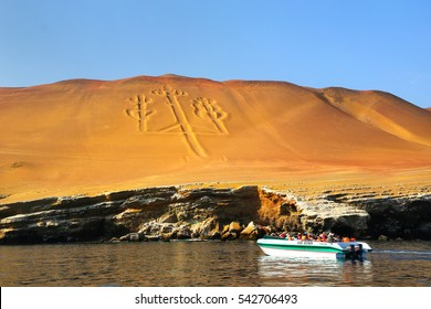 PARACAS, PERU-JANUARY 26: Unidentified people look at Candelabra of the Andes on January 26,2015  in Pisco Bay, Peru. Candelabra is prehistoric geoglyph found on the northern face of Paracas Peninsula