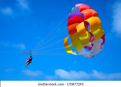 A parachute being towed at sea with a clear blue sky in the background.