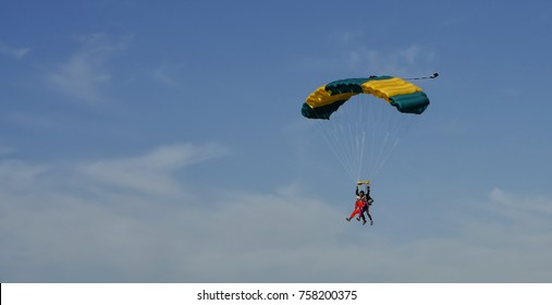 Parachute flights in the blue sky. Skydiving in tandem with a yellow-green parachute.