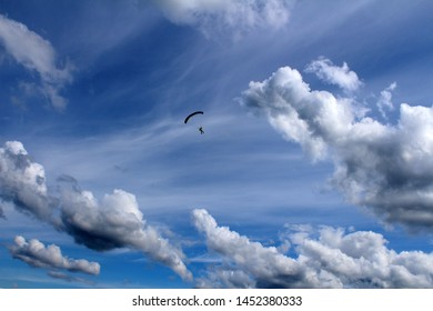 A parachute is flying near amazing clouds.